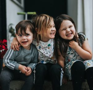Three toddlers with their arms around each other laughing